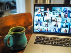 a coffee cup next to a laptop with zoom video call