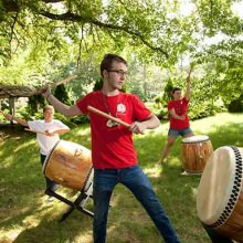 Villagers practice Taiko drumming under the trees.