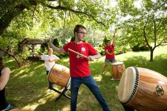 <p>Villagers practice <i>Taiko </i>drumming under the trees.</p>