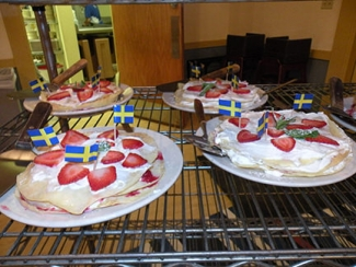 <p>Delicious <i>pannkakstårtor </i>(pancake cakes) decorated with <i>svenska flaggor</i> (Swedish flags) await hungry villagers!</p>