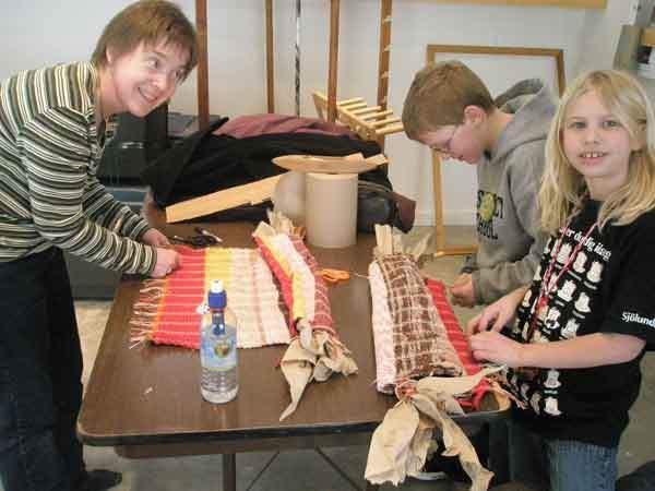 Family program participants in the weaving studio