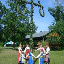 Villagers and staff in traditional Swedish costumes standing around the majstång (may pole).