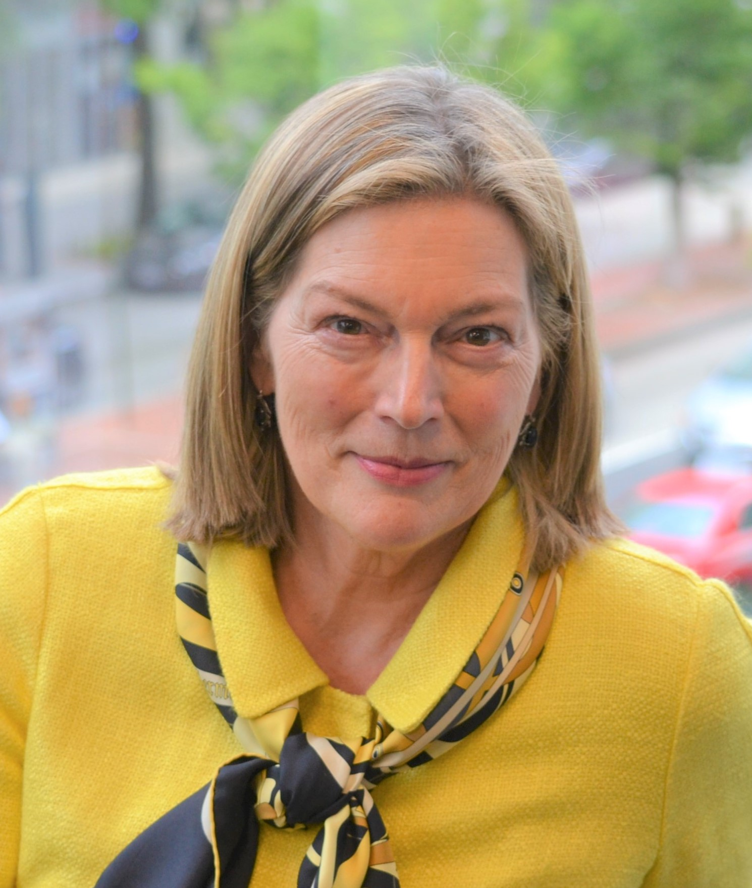 A headshot of Ambassador Stephens wearing a yellow blazer.