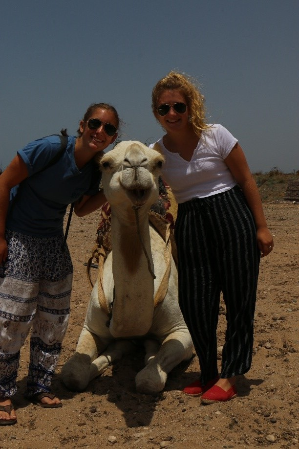 Two young American women pose with a white camel