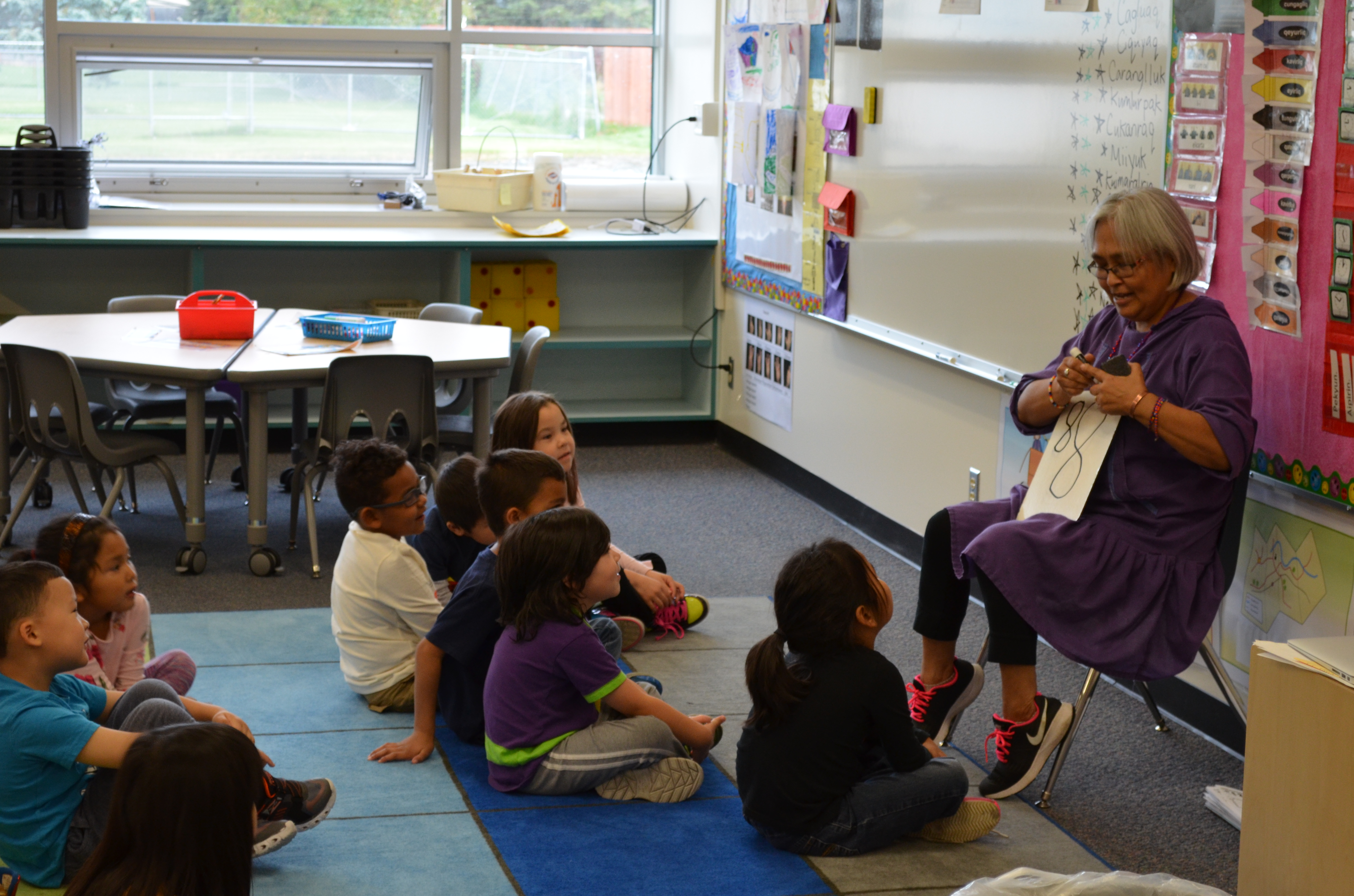 A teacher in the Yup'ik immersion program guides a group of kindergarten students seated on mats.