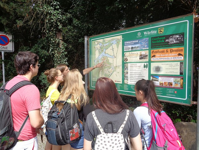 German credit abroad students read a park map.