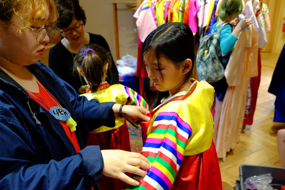 A Korean counselor helps a villager try on a traditional Korean dress.