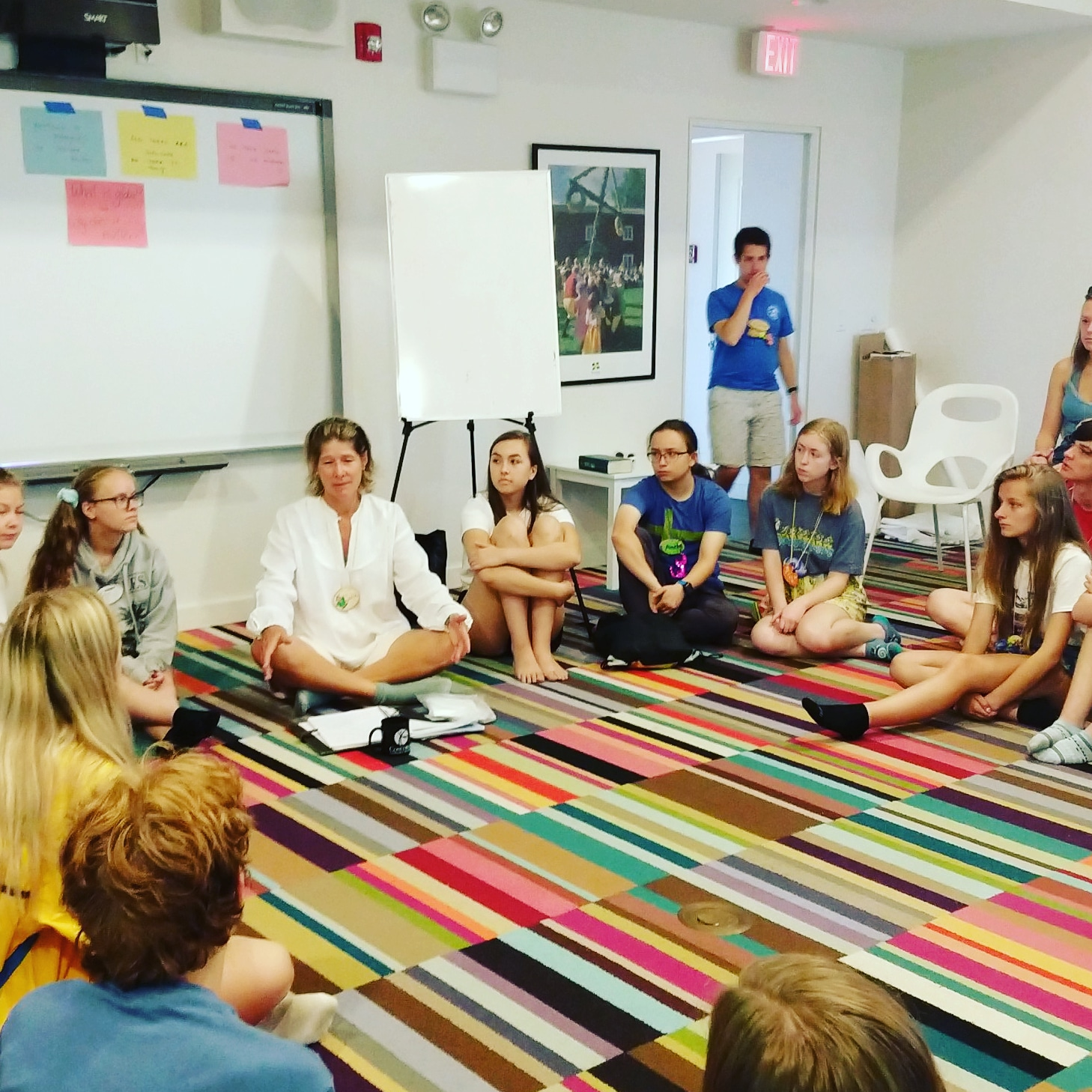 Students sit on the floor in a circle with Julie Lindah