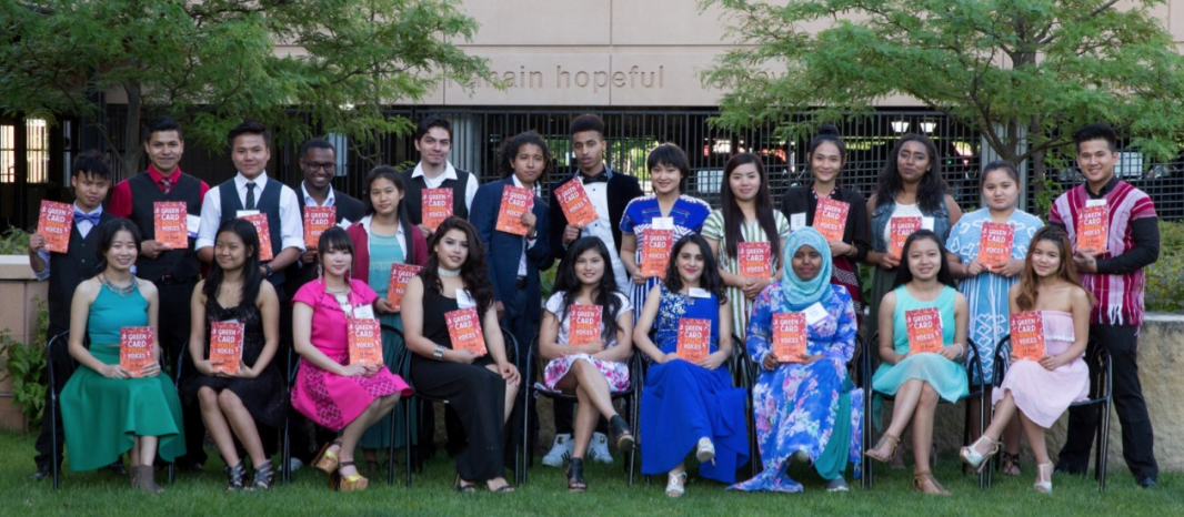 Students pose in front of their school, holding copies of Green Card Youth Voices.
