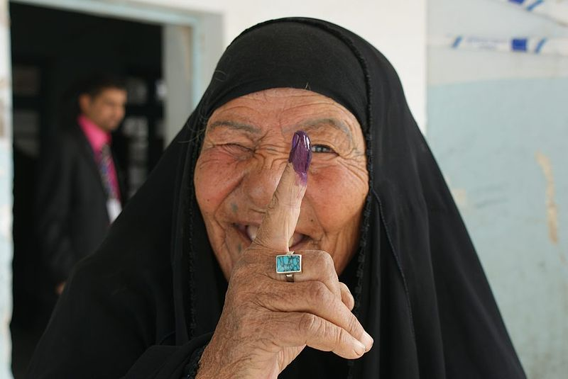 An elderly Afghani lady displays her finger covered in purple ink, showing she has voted.