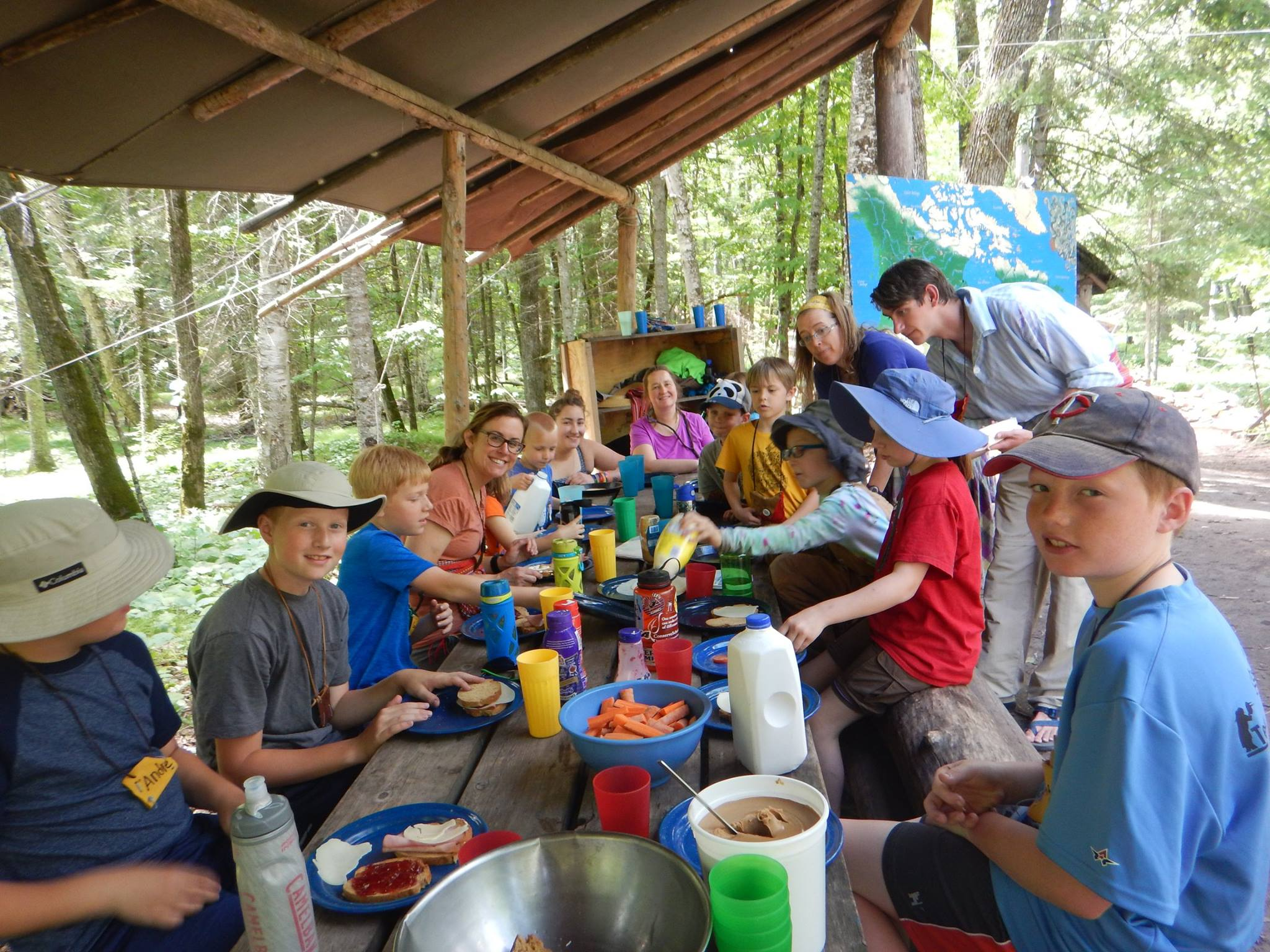 Boys enjoy a lunch in the woods, around a picnic table and under a canvas awning.